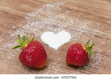 Fresh strawberry on a wooden table; heart from powdered sugar