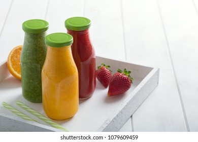Fresh strawberry, orange and broccoli smoothie in glasses with fruits and vegetables on a white wooden rustic background. Freshly blended summer drinks nice to detox and dieting. Copy space for text