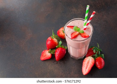 Fresh strawberry smoothie or milkshake and berries on old retro background. View with copy space, selective focus. Healthy Eating concept
