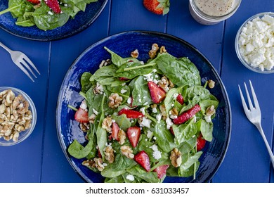 Fresh strawberry spinach salad with walnut and feta cheese and poppy seed dressing sitting on dark blue plate on dark blue background