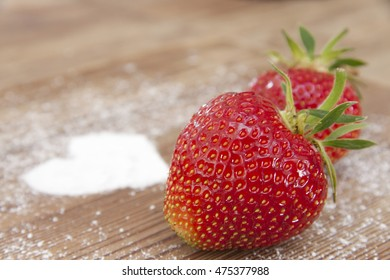 Fresh strawberry with sugar on a wooden table
