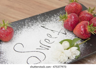 Fresh strawberry with sugar in a plate on a wooden table; an inscription from powdered sugar the sweet