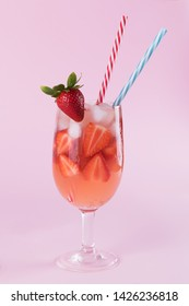 Fresh strawberry summer cocktail and ice cubes. Glass with strawberry, ice and wine - strawberry sangria on a pastel pink backgound, minimalism
