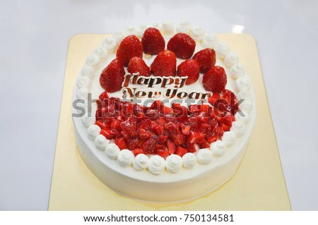 fresh strawberry topping decorated on whipped cream homemade vanilla cake and happy new year label on