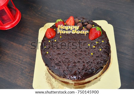 fresh strawberry topping decorated on cocoa cream homemade chocolate cake and happy new year label on