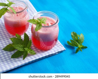 Fresh strawberry and watermelon juice decorated with mint on checkered table cloth and blue wooden background