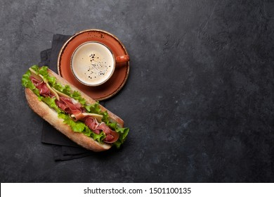 Fresh submarine sandwich with prosciutto ham, cheese and lettuce with coffee cup on stone background. Top view with copy space for your text
