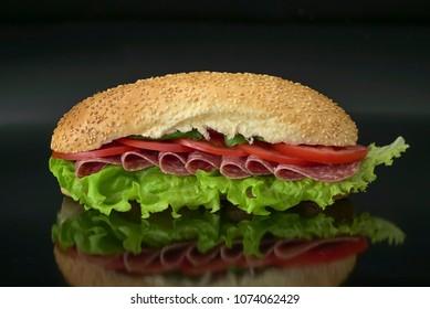fresh submarine sandwich with salami, tomatoes, lettuce on black background