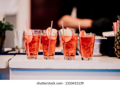 Fresh summer alcoholic drinks, long cocktails with strawberry flavour, apple cider and ice