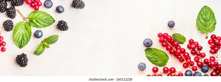 Fresh summer berries, corner frames on white wooden background, top view, banner for website