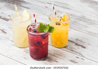 Fresh summer blueberries, pear and orange lemonade cocktails garnished with fresh mint leaves, fruits and straws. Cold refreshing drinks or beverages in glass jars with ice on rustic white table.