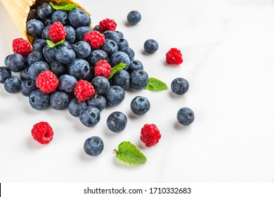 Fresh summer blueberries and raspberries with mint in waffle cone on white marble background. summer food concept. close up with copy space.