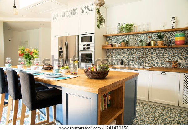 Fresh summer breakfast in Mediterranean style kitchen. Bright and sunny space with a lot of herbs and plants. Modern kitchen with open space.