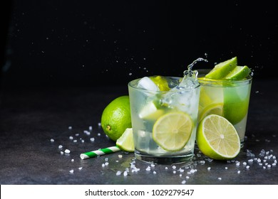 fresh summer caipirinha cocktail with splash on a black background. green fruit lime on table