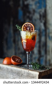 Fresh summer cocktail with red oranges in a glass on rustic background. Fresh  cocktail. Cocktail with gradient