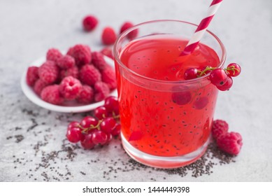 Fresh summer detox cocktail drink with red currant and raspberrry and chia seeds on a stone table.