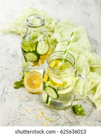 Fresh Summer Drink. Healthy detox drink with cucumber, lemon and celery in a glass jar and bottle on a white background