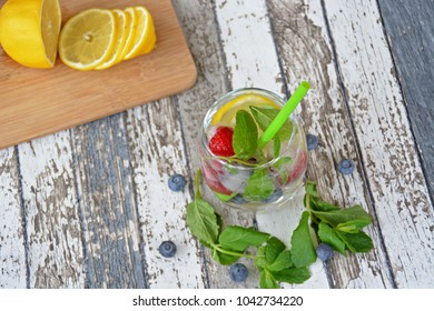 Fresh summer drink made out of mint, raspberry, citrus and blueberry