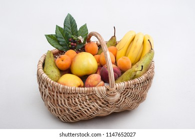 Fresh summer fruit set in a wooden basket on a white background
