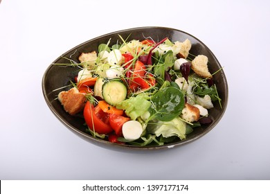 Fresh summer salad with arugula and red cherry tomatoes, olives and mozzarella.