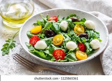 Fresh summer salad with arugula, yellow and red cherry tomatoes, Kalamata olives and mozzarella. Selective focus
