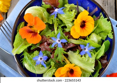 Fresh summer salad with edible flowers nasturtium, borage flowers in a bowl. Top view.