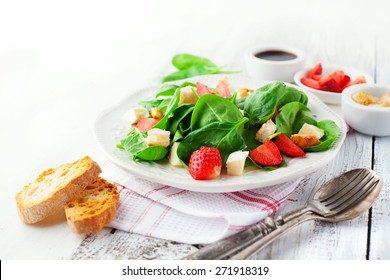 Fresh summer salad with strawberries, spinach leaves and feta cheese on white wooden background, selective focus