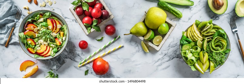 Fresh summer salads with avocado, kiwi, apple, cucumber, pear, peach, micro greens, spinach, feta cheese on light marble background. Healthy food, clean eating, Buddha bowl salad, top view