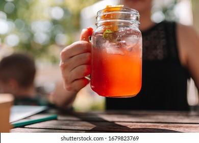 Fresh summer strawberry homemade lemonade in woman hand on sunny day garden party