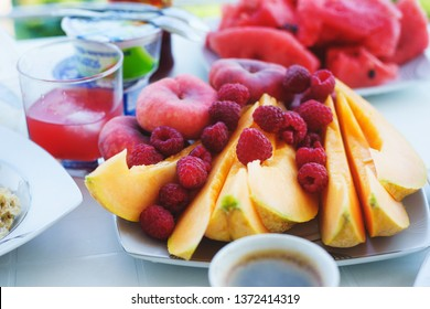 Fresh summer traditional breakfast is fragrant black coffee with fruits, watermelon and melon on the table. Healthy diet and vegetarian diet. Journey. Summer holidays by the sea