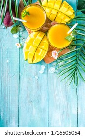 Fresh summer tropical fruit drink. Mango smoothie or mango juice, with fresh mango and tropical leaves on outdoor wooden background. Copy space top view.