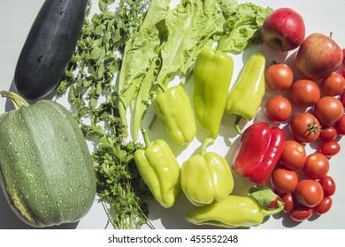 Fresh summer vegetables harvest from garden. Top view on multiple kinds of vegetables lying on white wooden table.