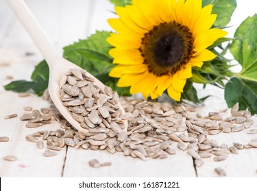 Fresh Sunflower Seeds (Macro Shot on wooden background)