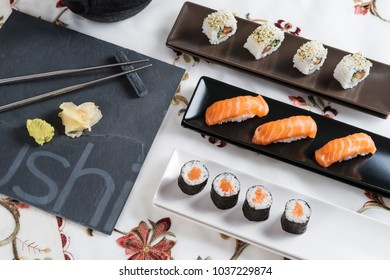 Fresh sushi presented on specific tableware with stone plate and silver chopsticks, variation of salmon maki, nigiri and sushi roll on oriental table set