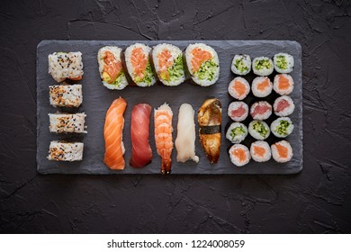 Fresh sushi rolls set with salmon and tuna fish served on black stone board. Top view of traditional japanese cuisine.
