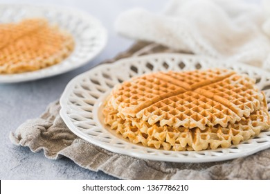 Fresh swedish golden waffles with nothing on top. White patterned plate, gray background and a piece of linen cloth underneath the plate. There is another plate defocused in the background.