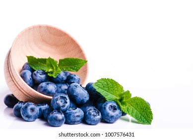 Fresh sweet blueberry fruit and leaf of mint.. Dessert healthy food. Group of ripe blue juicy organic berries. Raw summer diet. Delicious nature vegetarian ingredient. Wooden background.