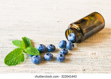 Fresh sweet blueberry fruit and leaf of mint in medical bottle from pills. Dessert healthy food. Group of ripe blue juicy organic berries. Raw summer diet. Delicious nature vegetarian ingredient