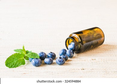 Fresh sweet blueberry fruit and leaf of mint in medical bottle from pills. Dessert healthy food. Group of ripe blue jui?y organic berries. Raw summer diet. Delicious nature vegetarian ingredient
