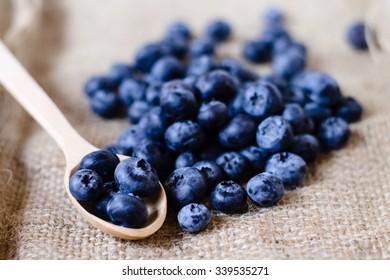 Fresh sweet blueberry fruit in spoon. Dessert healthy food. Group of ripe blue juicy organic berries. Raw summer diet. Delicious nature vegetarian ingredient.