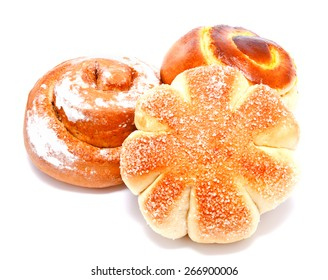 Fresh sweet buns and rolls with cream and cinnamon isolated on a white