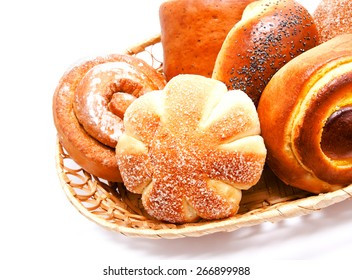 Fresh sweet buns and rolls with poppy and cream in the basket isolated on a white