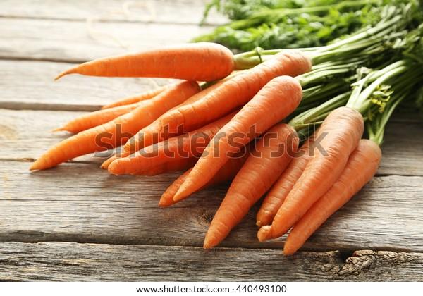 Cenoura fresca e doce em uma mesa de madeira cinza