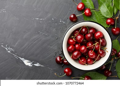Fresh sweet cherries bowl with leaves in water drops on stone background, top view