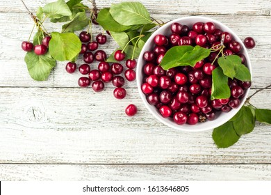 Fresh sweet cherries bowl with leaves in water drops on white wooden background, top view
