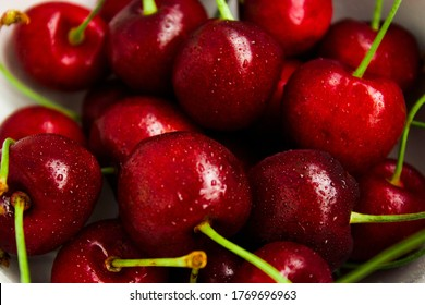 A lot of fresh sweet cherry fruit berries with water drops, close up. Pile of ripe cherries. Large collection of fresh red cherries. Ripe cherries texture background