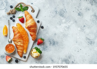 Fresh sweet croissants with butter and orange jam for breakfast. Continental breakfast on a white concrete table. Top view with copy space. Flat lay.