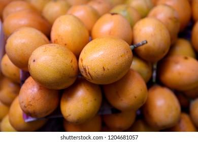 Fresh sweet Granadilla fruit, or Passiflora ligularis in a farmers produce market in Medellin, Colombia / South America.