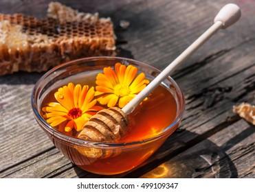 fresh sweet honey with stick and calendula flowers n glass bowl