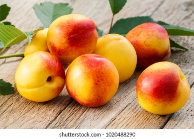 Fresh sweet nectarines with fresh green leaves on wooden background in the garden, ripe peaches, organic gardening